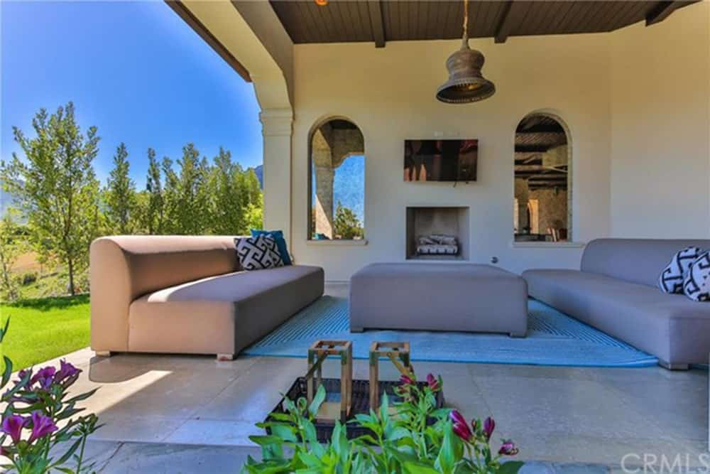 This lovely patio is open to the lush green landscaping outside. It has a couple of beige couches that match the beige marble flooring and walls that are contrasted by the chocolate brown ceiling bearing a bell-like pendant light over the green area rug.
