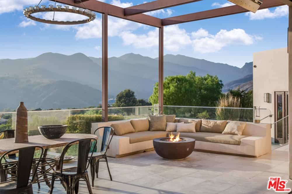 This charming outdoor patio has a stunning mountain view in the background augmented by low glass walls surrounding the area. There is a corner sofa with beige cushions and pillows facing a simple bowl firepit.