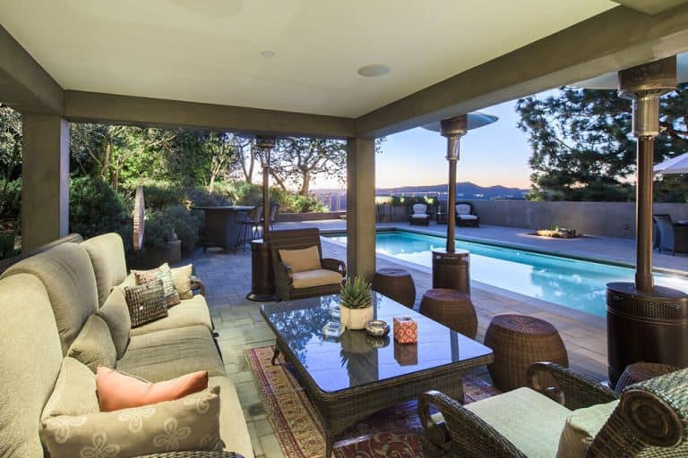 This is a comfortable patio beside the pool that has concrete blocks for flooring topped with a red patterned area rug complementing the huge gray sofa paired with a glass-top coffee table with the same woven wicker material as the other furniture.