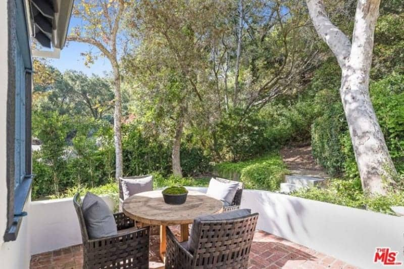 The red brick flooring is contrasted by the low white walls surrounding this charming little area that features a lush landscaping of trees and bushes that complements the round wooden table and its woven armchairs.