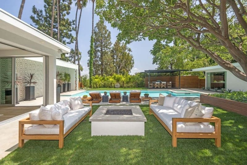 This is a charming patio under the shade of a large tree that has grass flooring contrasting the white firepit that is flanked by a pair of wooden benches with white cushions. This has a lovely poolside background framed with trees and bushes.