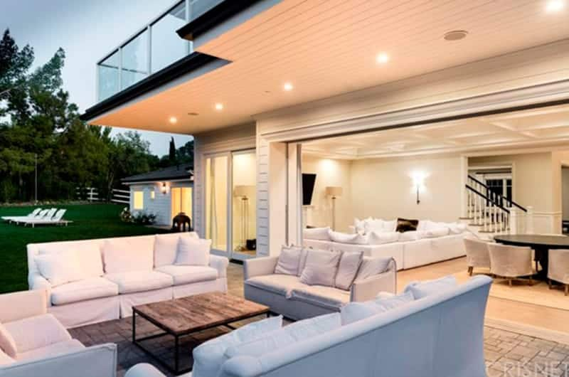 This brilliant patio is dominated by the white hues of the sofas that have white slipcovers matching with the white pillows all surrounding a wood-top coffee table with black iron legs contrasting the concrete flooring.