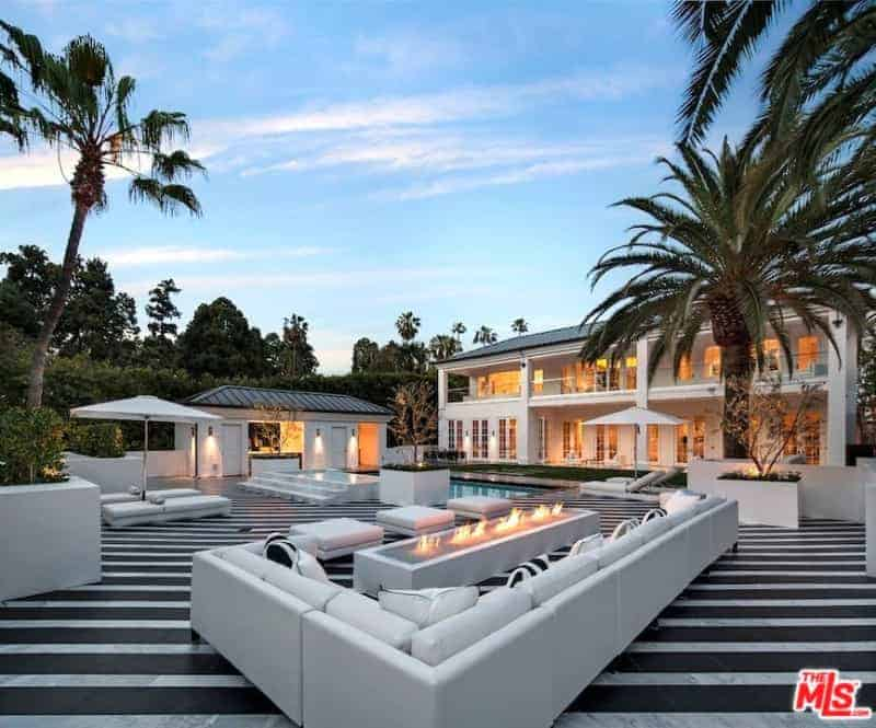This is a massive backyard showcasing a pool that is surrounded by a large flooring dominated by black and light gray stripes setting a nice background for the solid white furnitures and structures.