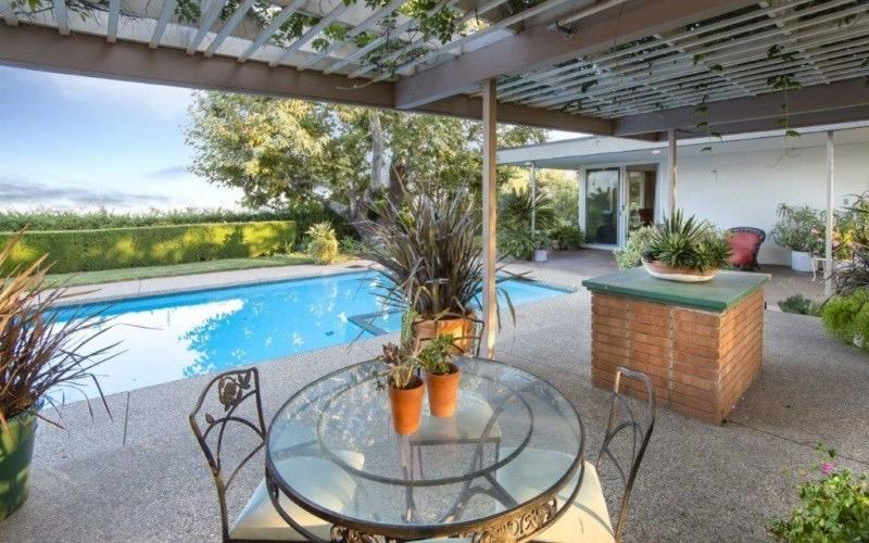 This is a large area by the pool that has trellises topped with plants that set the theme of the potted plants adorning the concrete flooring along with a bricked pedestal bearing a potted plant beside the glass-top round table with wrought iron chairs.