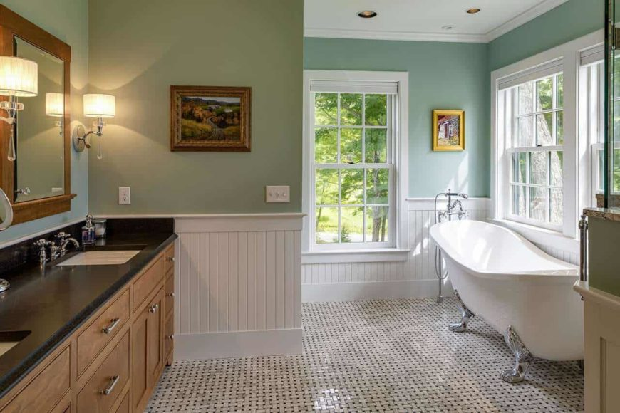 This simple bathroom has a white wainscoting to complement the light green walls. These white wainscoting blends well with the bright white freestanding bathtub at the corner. It has elegant silvery legs that stand out against the black and white patterned flooring tiles.
