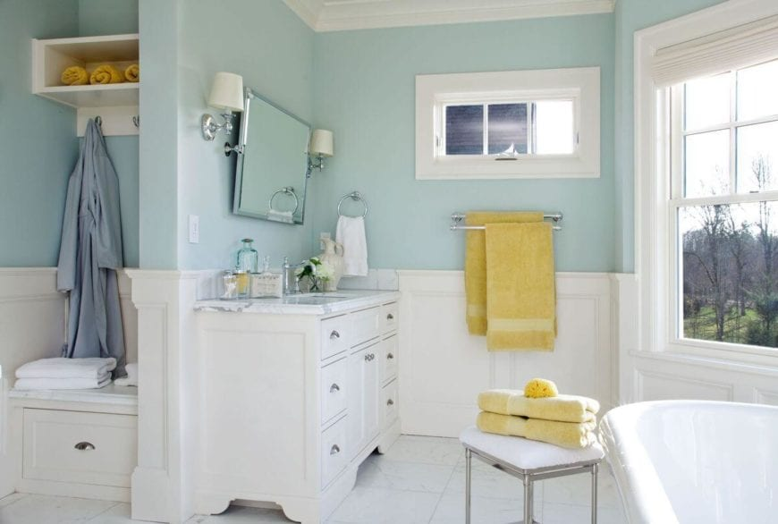 This is a bright and cheerful Country-style bathroom with white wainscoting to complement the light blue walls and blend with the white wooden vanity and white freestanding bathtub by the window. The vanity is paired with a wall-mounted mirror flanked by wall lamps.