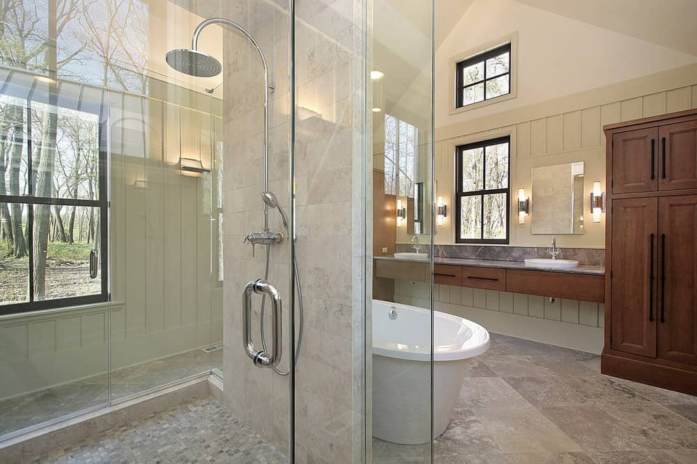 Light and airy primary bathroom with limestone flooring and aluminum framed windows overlooking a serene outdoor view. It has a wooden sink vanity and a walk-in shower placed behind the freestanding bathtub.