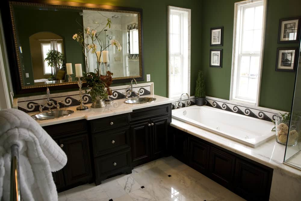 Classic green bathroom boasts a large mirror and dual sink vanity that matches the drop-in bathtub accented with black framed photos.