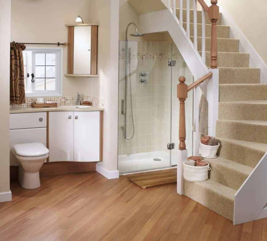 A wooden staircase covered in beige carpet leads to this cozy bathroom with a walk-in shower and a toilet attached to the white sink vanity.