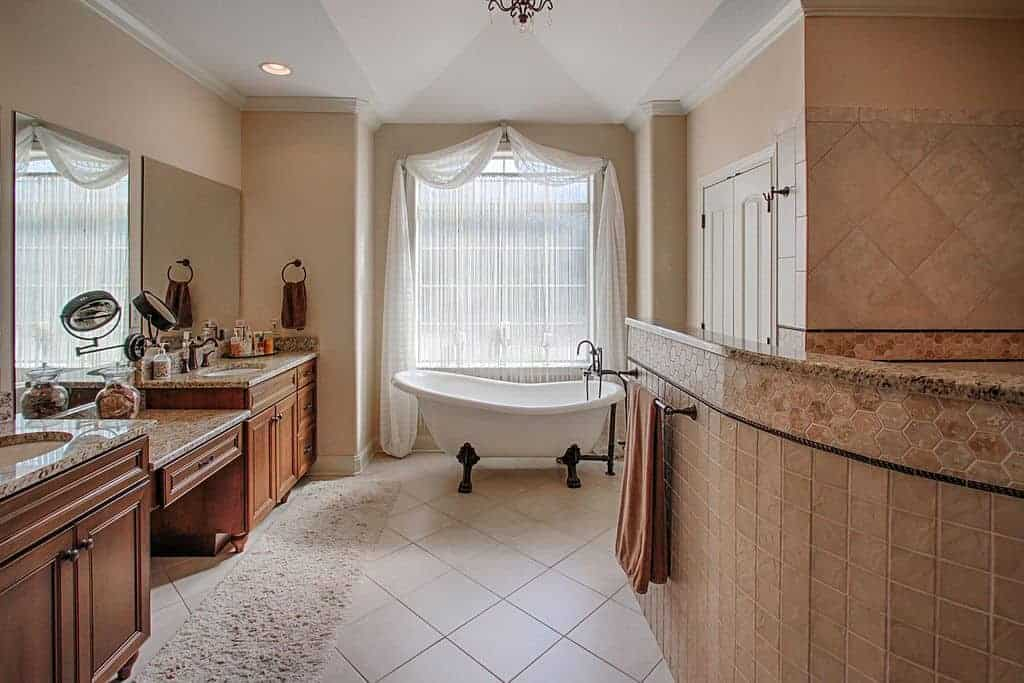 Country style bathroom with vaulted ceiling and white tiled flooring lined with a shaggy runner. It has dual sink vanity and a clawfoot tub by the glazed window covered in white sheer curtains.