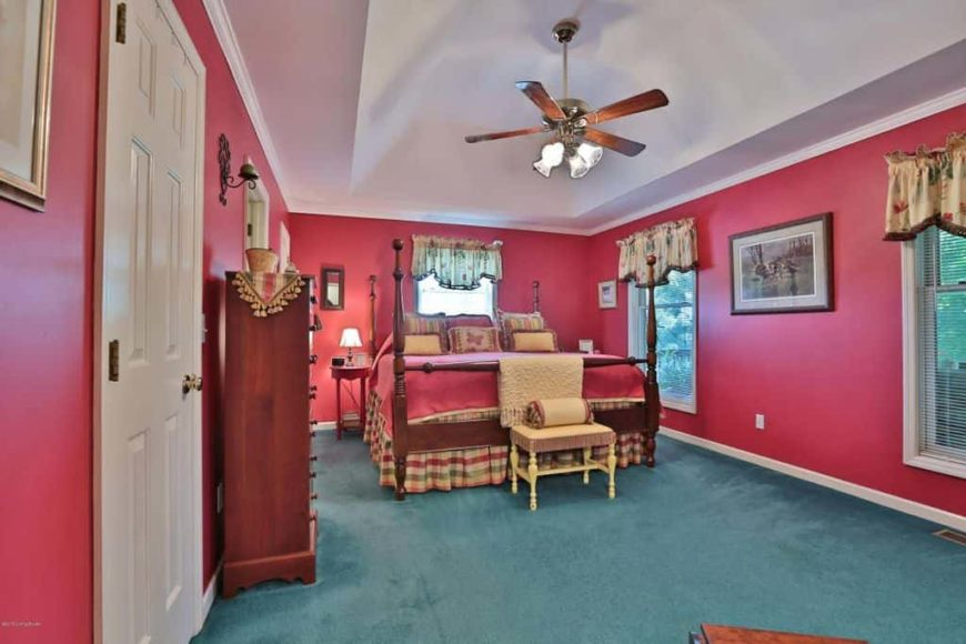 Country style primary bedroom featuring red walls and green carpet flooring. It offers a large classy bed along with cabinetry on the side.