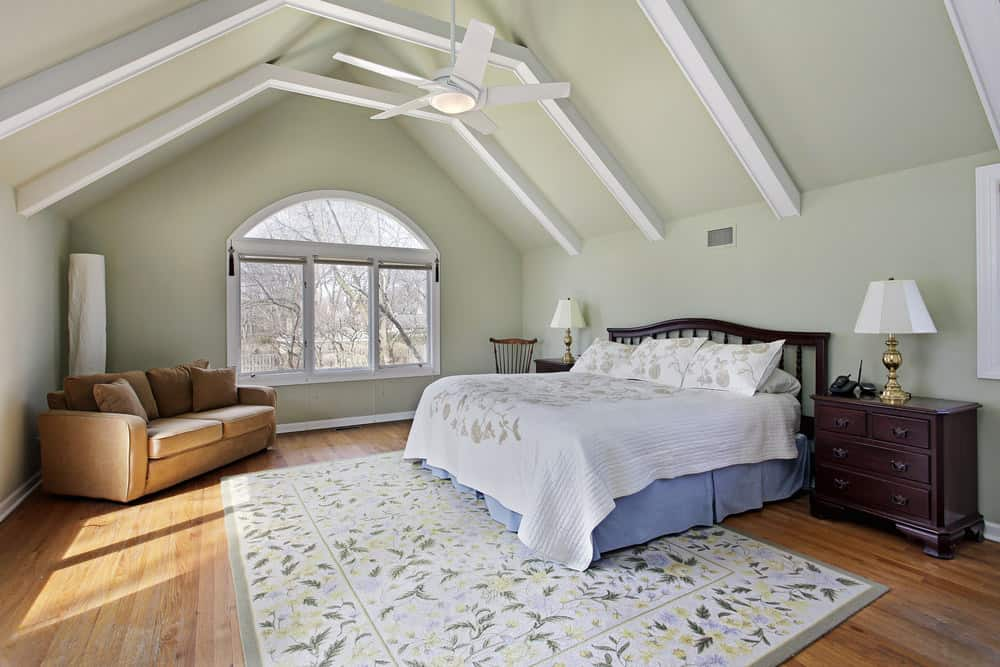 Spacious primary bedroom featuring hardwood flooring and a vaulted ceiling with beams. It offers a large bed along with a brown couch in the corner.