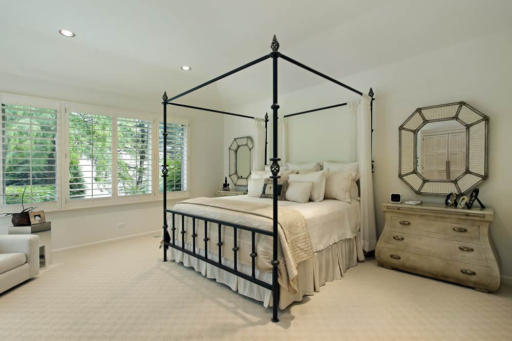 Large Country style primary bedroom featuring classy carpet flooring and white walls. It has a nice bed along with rustic side tables.