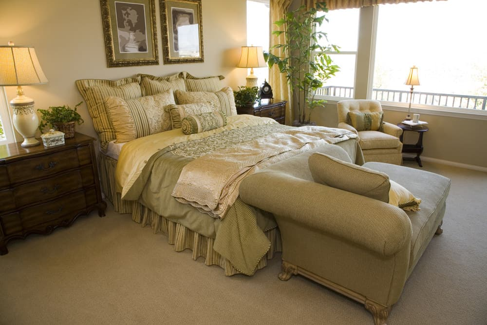 A focused shot at this primary bedroom's large classy bed with a couch at the edge. The bed setup is lighted by a couple of table lamps that look elegant.