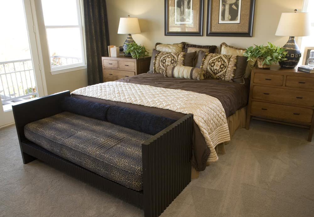 A close up look at this primary bedroom's bed setup with a couch at the edge, set on the gray carpet flooring.