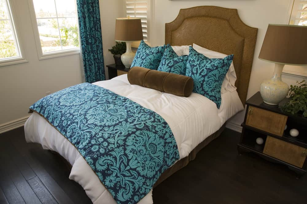 A focused shot at this primary bedroom's classy double-sized bed with a blue accent lighted by brown table lamps matching the brown bed frame.