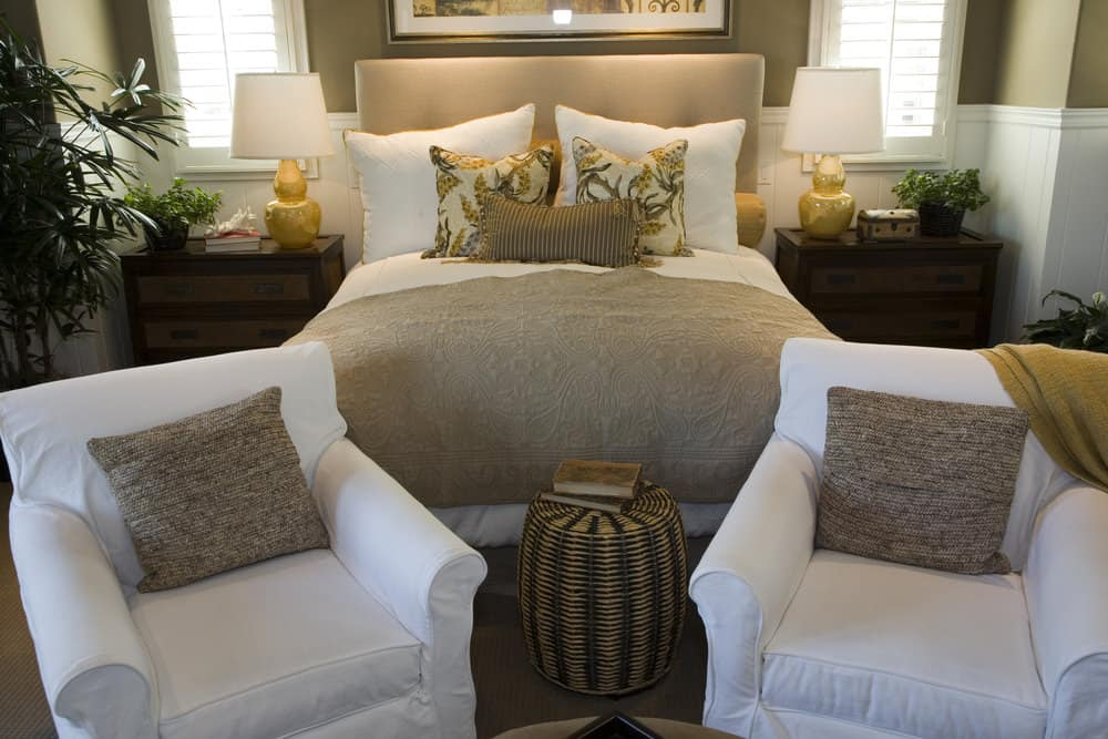 A focused look at this primary bedroom's large bed setup with a pair of white seats at the edge of the bed.
