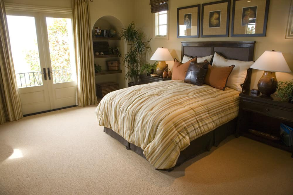 Spacious primary bedroom featuring a classy bed setup along with built-in shelving on the side. The room features a tall ceiling and carpeted flooring.