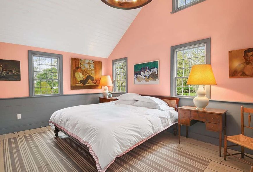 Country style primary bedroom featuring orange walls and hardwood flooring topped by an area rug, along with a tall white ceiling. The bed is lighted by table lamps on both sides.