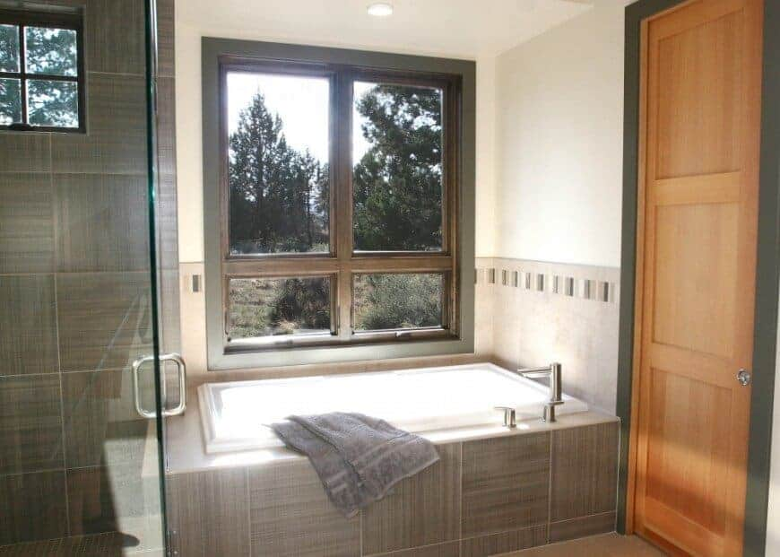 Beside the glass enclosed shower area is the white bathtub housed with gray tiles that is complemented by a window with elegant wooden frames that matches the design of the redwood door framed the same as the window.