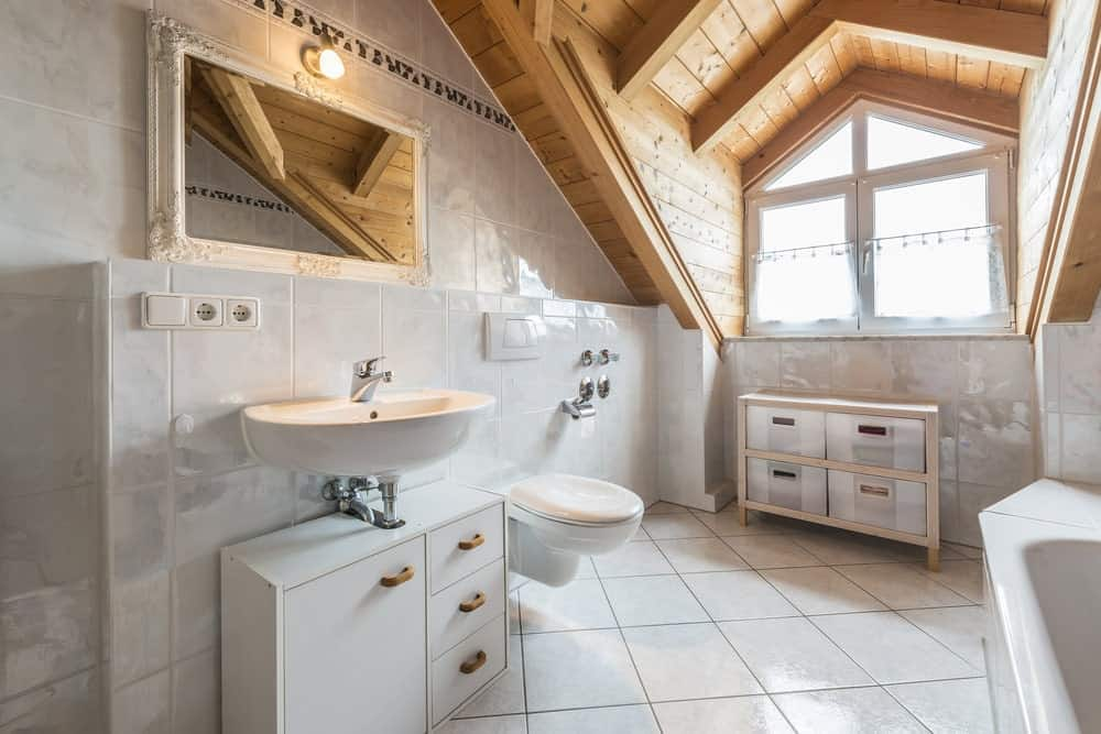 This charming craftsman-style bathroom has a wooden cathedral ceiling with exposed wooden beams due to the arched dormer window that brings in natural lighting on the sleek white tiles that are complemented by the white bathtub, sink and floating toilet.