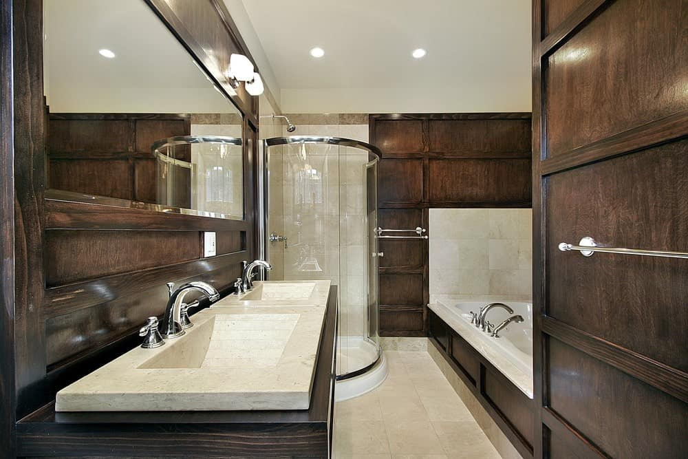 The walls of this elegant craftsman-style bathroom has a dark wooden finish that extends to the housing of the white porcelain bathtub as well as the two-sink vanity and its large embedded mirror beside the glass enclosed shower area.