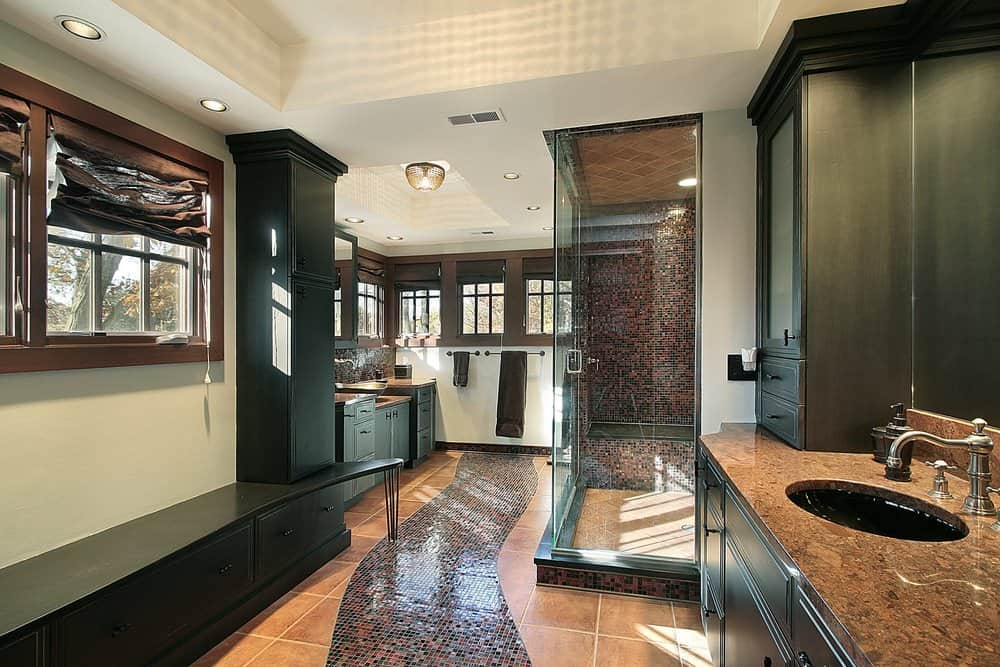 The white ceiling and walls of this craftsman-style bathroom is contrasted by the elegant wooden frames of the row of windows that shine natural lights on the two wooden vanities that has black cabinets and drawers topped with brown marble countertops.