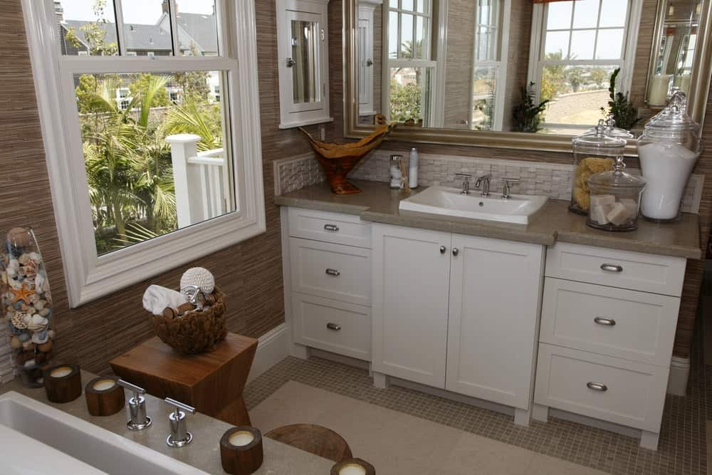 Across from the white bathtub that is embedded in gray marble is the white wooden vanity with beautiful shaker cabinets and drawers topped with the same gray hue as the gray flooring tiles that pairs well with the brown wallpaper.