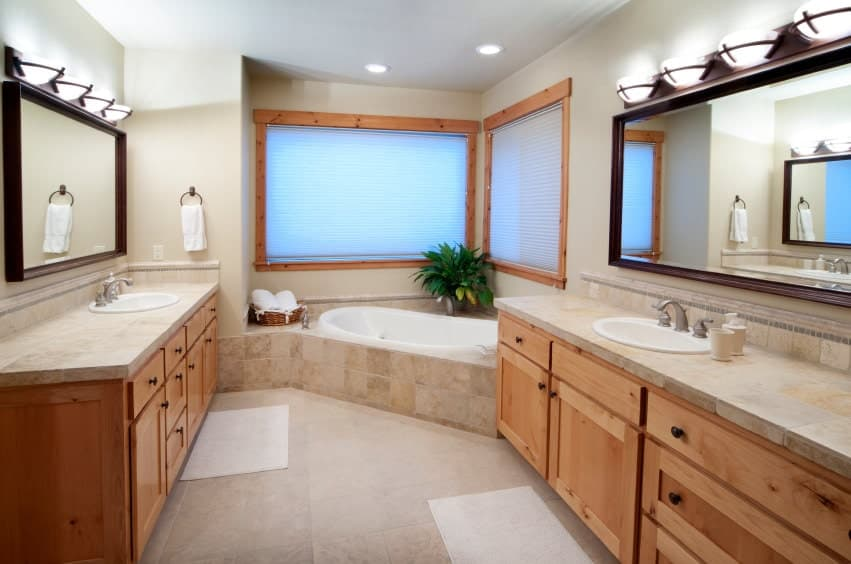 There is a corner bathtub inlaid with the same beige marble as the countertops of the two vanity areas with wooden cabinets and drawers. This pairs well with the frames of the two windows of the bathtub's alcove corner adorned with a potted plant.