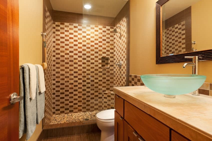 The frosted glass bowl basin of the sink stands out against the beige countertop of the wooden vanity complementing the brown flooring tiles. The shower area has a checkered pattern on its walls with the same brown hue as the flooring.