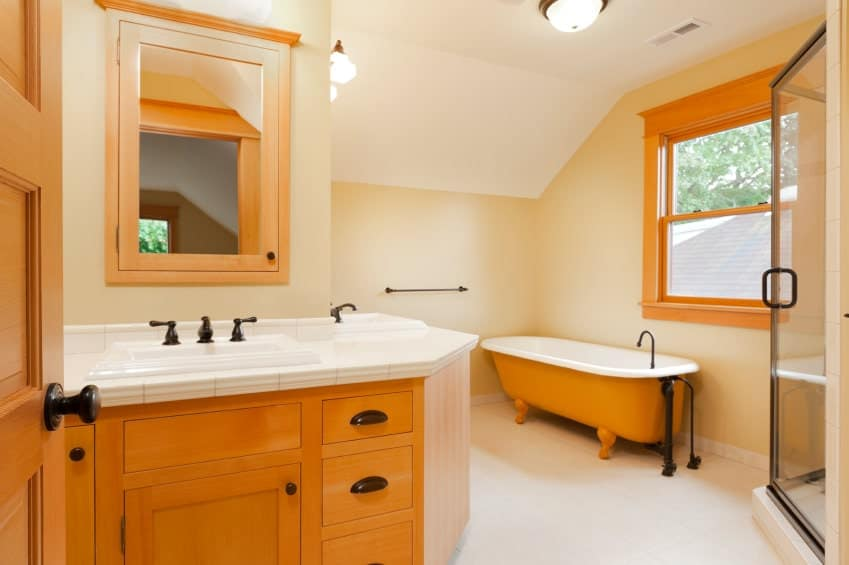 The orange hue of the freestanding bathtub in the beige corner matches with the orange hue of the wooden L-shaped two sink vanity that follows the lay of the corner topped with white tiles for its countertop across from the glass door of the shower area.