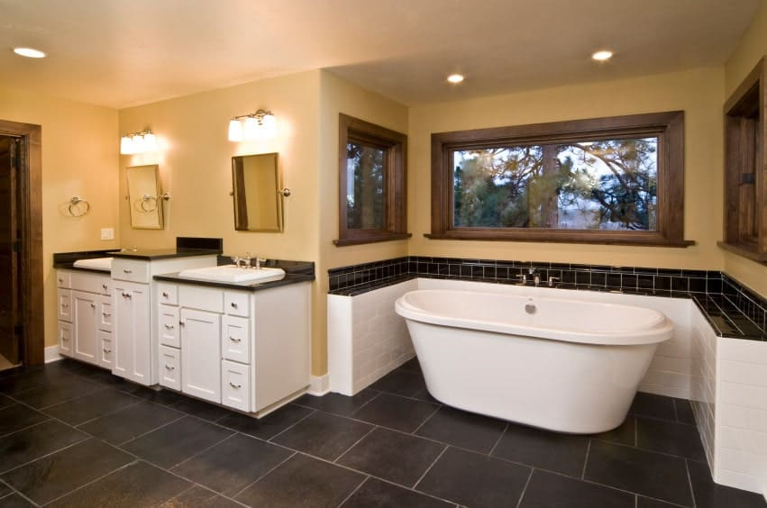 The beautiful black tiles of the flooring contrasts with the white two-sink vanity that has small drawers and cabinets topped with black countertops to retain the aesthetic as the white freestanding bathtub in an alcove of black and white tiles.