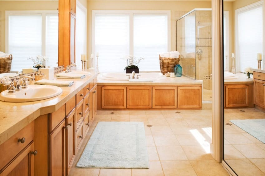 The brilliant white windows that has white blinds above the bathtub brings in natural light that brightens the beige flooring tiles complemented by the wooden two-sink vanity attached to the wooden housing of the bathtub.