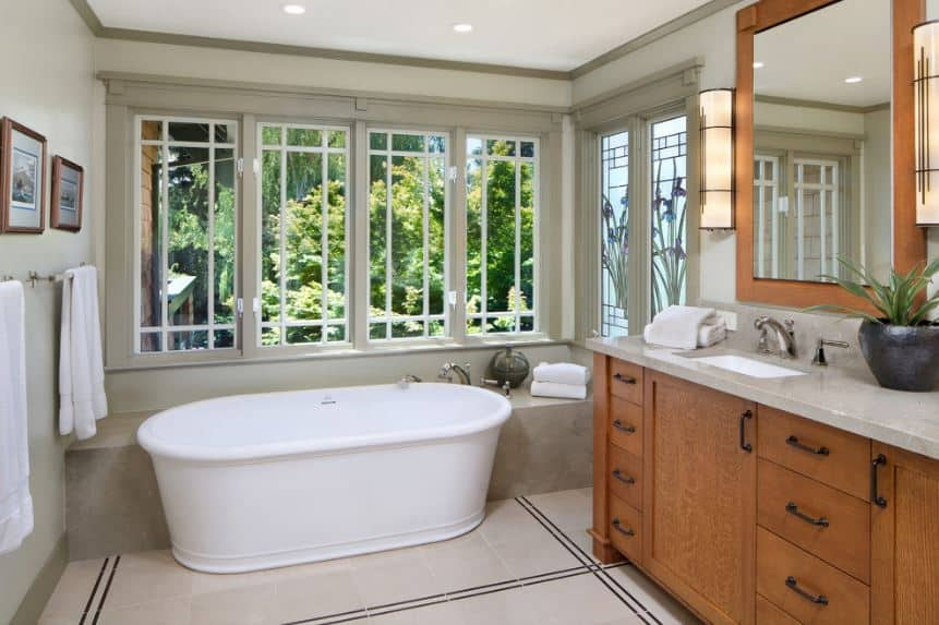 The rectangular vanity mirror that is flanked with modern wall-mounted lamps has a wooden frame that matches with wooden cabinets and drawers of the vanity that stands out against the white tiles of the flooring complemented by a stark white freestanding bathtub.