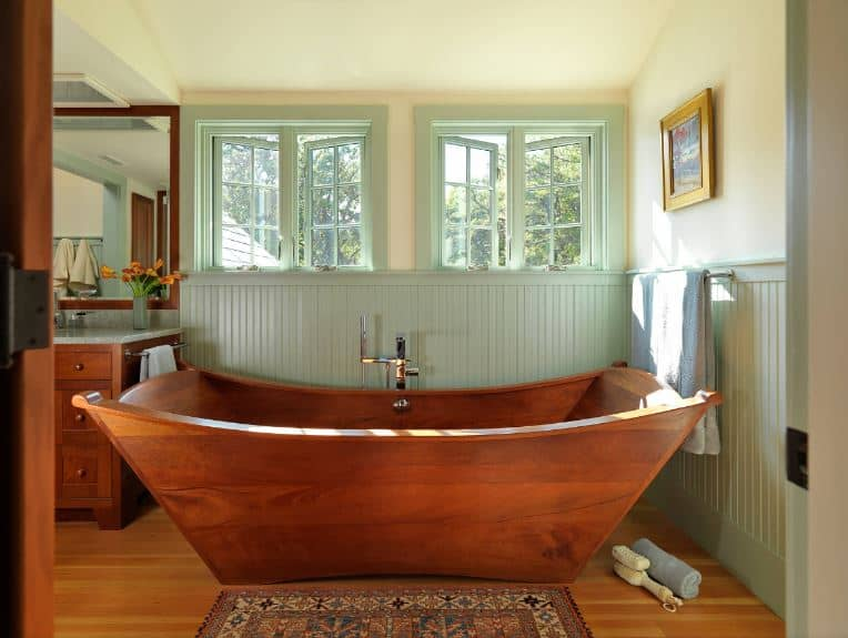 The wooden freestanding bathtub showcases superb craftsmanship matching with the wooden vanity that stands out against the light green wainscoting extending to the framed of the windows complemented by the beige upper walls.