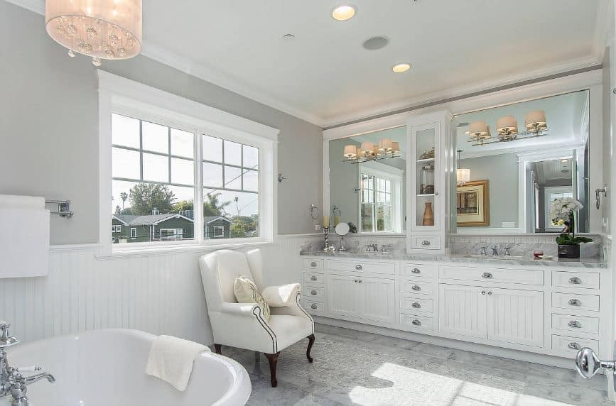 The gray walls are brightened by the white wainscoting that has an elegant white wooden finish that fits with the large white vanity that has silver handles on its cabinets and drawers matching the fixtures of the bathtub across the vanity.