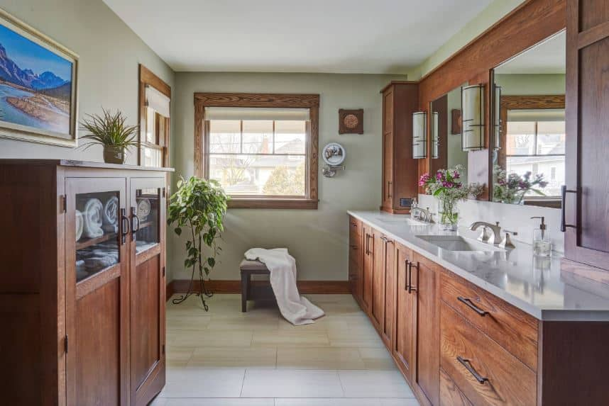 On one of the green walls is a small wooden cabinet with glass panels on it for towel storage topped with a colorful painting. Across from it is a large two-sink vanity with the same wooden finish and dark handles that contrast the white countertop.