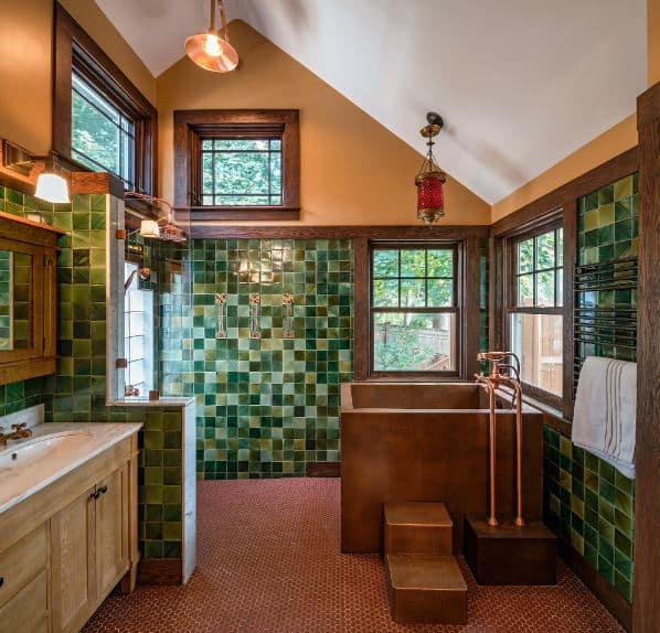 The white cathedral ceiling is contrasted by the earthy hue of the upper walls paired with wood-framed windows. This is complemented by the beautiful lower part of the walls filled with tiles of various shades of green serving as a nice background for the brass bathtub and the wooden vanity.