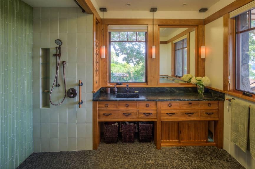 This craftsman-style bathroom has two sections. On the left side is the shower area that has light green bamboo-like wall tiles and the same stone mosaic flooring as the section on the right that is dominated by the large wooden structure of the vanity.