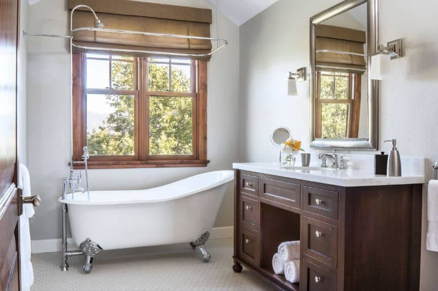 The white freestanding bathtub has stainless steel legs that match with the pipes, mirror frames and fixtures of the bathroom as well as the handles of the elegant wooden drawers of the dark vanity that is contrasted with a white countertop.