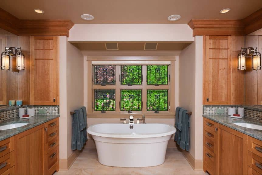 The white freestanding bathtub is placed within an alcove of light pink walls and windows that feature the lush greenery outside as a nice background for the two redwood vanities on either side that blends into the wooden moldings.