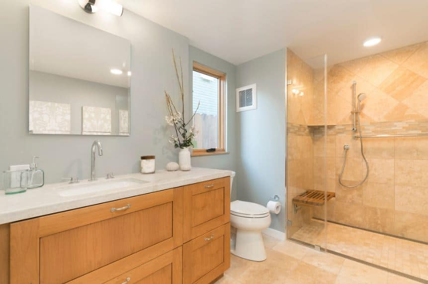 This lovely craftsman-style bathroom has a white ceiling and light blue walls that makes the elegant wooden vanity stand out. This complements the beige marble tiles of the floor that goes all the way to the walls of the glass-enclosed shower area.