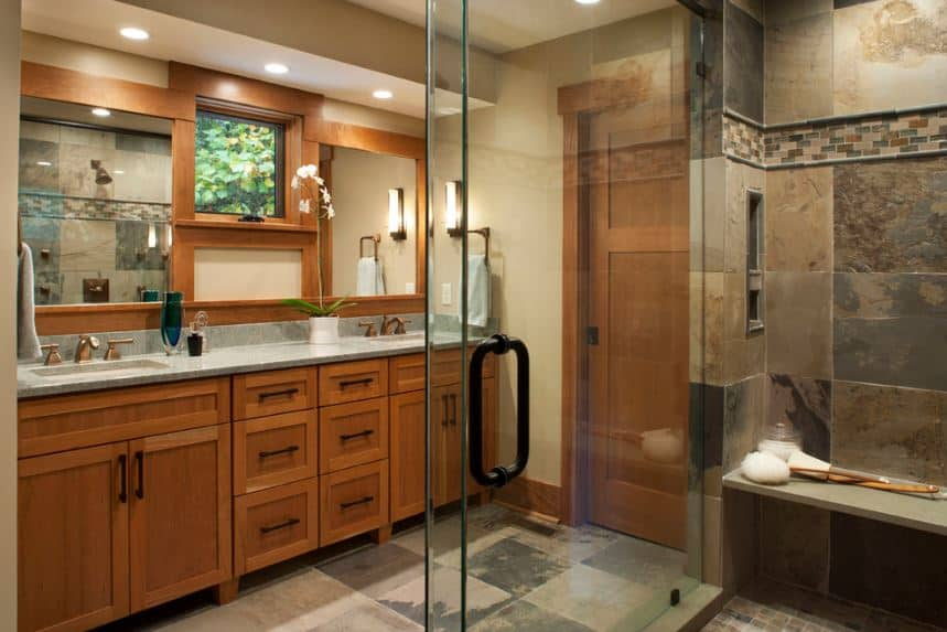 The glass enclosed shower area has gray and brown marble tiles that matches the flooring of the vanity area that is dominated by the amazing craftsmanship of the cabinets and drawers paired with the wooden framing of the wall-mounted mirrors.