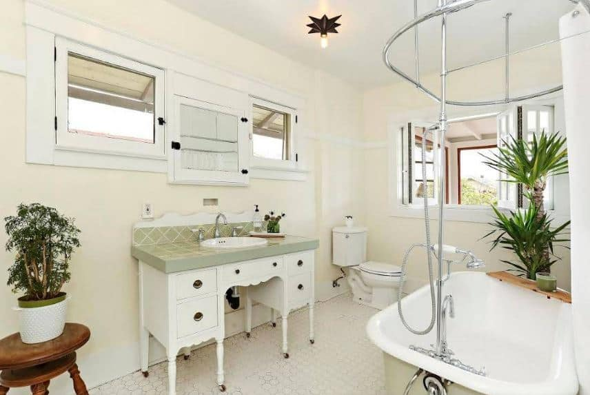 The beige walls of this craftsman-style bathroom are further lightened by the white ceiling, toilet and freestanding bathtub that matches with the white wooden vanity that has pencil legs with wheels complemented by an avocado green countertop.