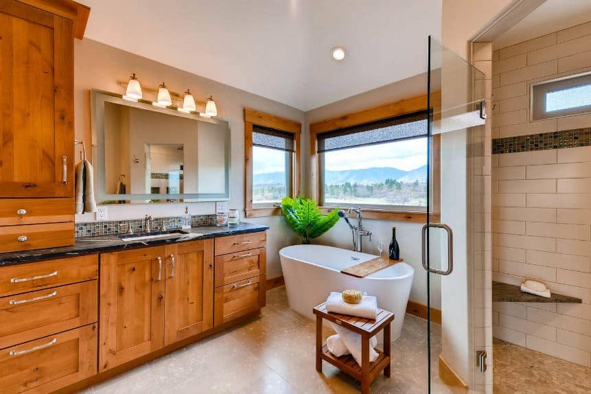 This bright bathroom is dominated by a large wooden structure that has elegant shaker cabinets and drawers topped with a black marble countertop housing the white faucet with a vanity mirror above illuminated by a row of wall-mounted lamps.