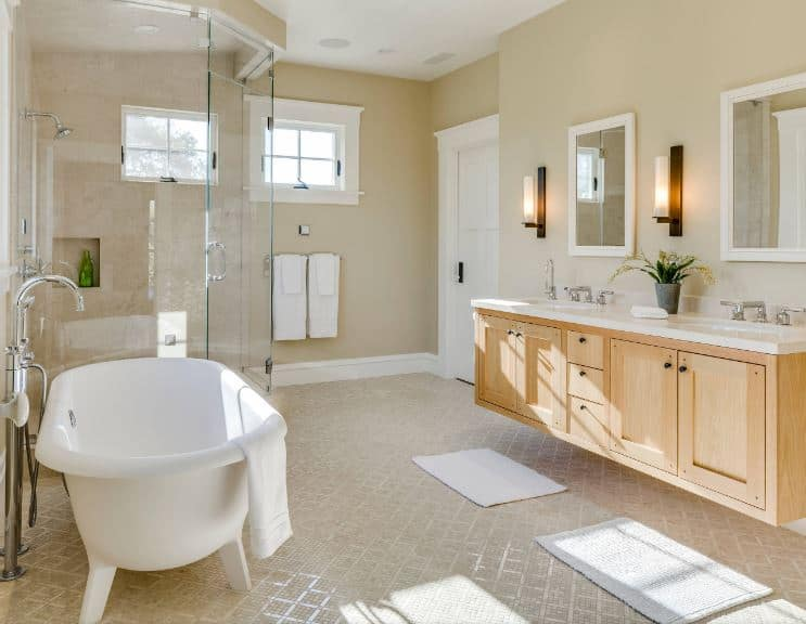 Beside the glass-enclosed shower area is the white porcelain freestanding bathtub stands on white legs across from the elegant floating wooden vanity with shaker cabinets and drawers under a white countertop that supports two sinks.