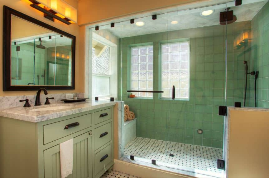 The large glass-enclosed shower area on the far wall has green tiles on its walls that matches perfectly with the avocado green cabinets and drawers of the vanity that has black handles matching the fixtures of the bathroom.