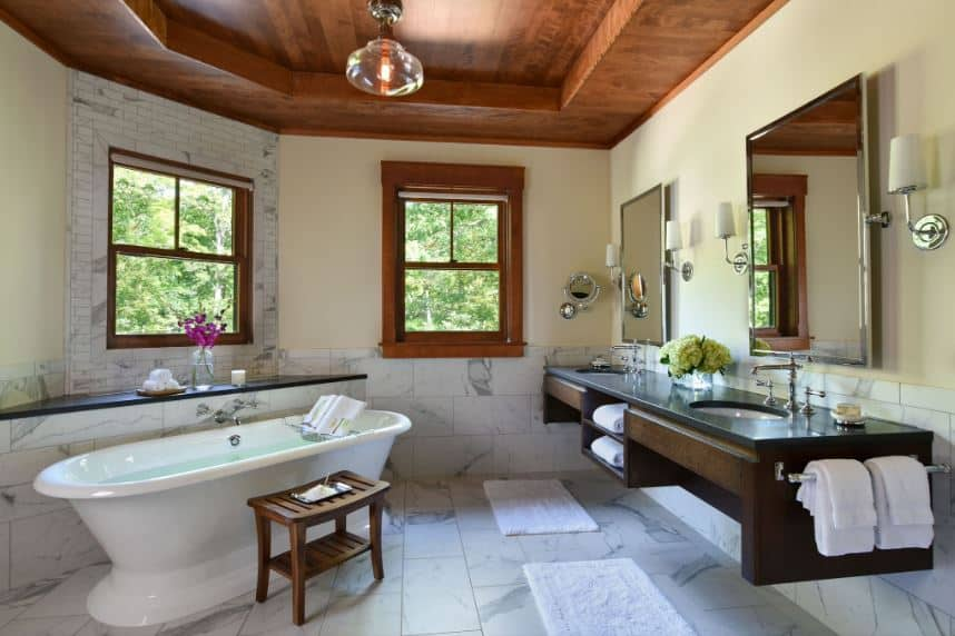 The wooden tray ceiling has an irregular shape that is followed by the beige upper walls and white marble lower walls extending to the flooring. This is contrasted by the floating wooden two-sink vanity that has shelves and racks attached to it.