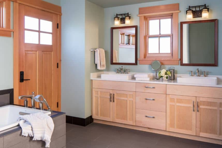 The wooden cabinets of the two-sink vanity has a beautifully-crafted design on it that matches with the wood-framed window and wooden door and its built-in glass window. This goes well with the delightful light blue walls contrasting the dark gray flooring.