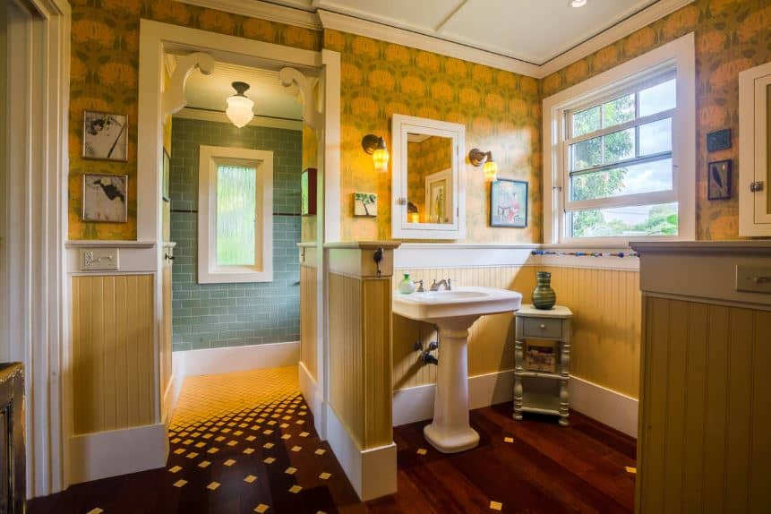 The brilliant yellow floor tiles of the shower area has a pattern slowly dispersing and transitioning to the hardwood flooring of the white pedestal sink in an alcove of yellow wooden wainscoting topped with yellow patterned wallpaper.